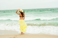 Beautiful girl in the yellow dress water beach Royalty Free Stock Photography
