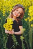 Beautiful girl with yellow flowers in the field. Little beautiful girl with yellow flowers in the field Stock Photos