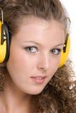Beautiful girl in yellow headphones. Beautiful curly girl in yellow headphones Stock Photos