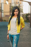 Beautiful girl in a yellow jacket and jeans holds glasses. Outdoor Royalty Free Stock Image