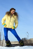 Beautiful girl in a yellow jacket in winter Royalty Free Stock Photo