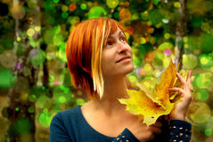 Beautiful girl with yellow leaves in hand on background with bokeh Royalty Free Stock Images