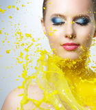 Beautiful girl and yellow paint splashes Stock Photos