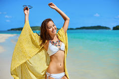 Beautiful girl with yellow pareo having fun on the beach Royalty Free Stock Image