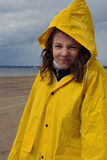 A beautiful girl in a yellow raincoat is standing in the rain in the spring on the shore of the bay and wrinkles her nose Stock Image
