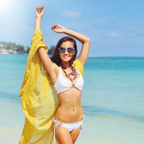 Beautiful girl with yellow scarf on the beach Royalty Free Stock Images