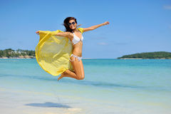 Beautiful girl with yellow scarf jumping on the beach. Travel an Royalty Free Stock Images