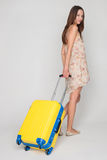 Beautiful girl with a yellow suitcase loves to travel Stock Photos