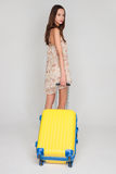 Beautiful girl with a yellow suitcase loves to travel Stock Photo