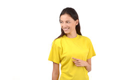 Beautiful girl with yellow t-shirt pointing to the side. Royalty Free Stock Photography