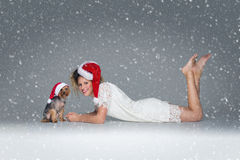 Beautiful girl with yorkie dog in santa cap Royalty Free Stock Photography