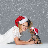 Beautiful girl with yorkie dog in santa cap Royalty Free Stock Images