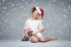Beautiful girl with yorkie dog in santa cap Stock Image