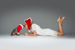 Beautiful girl with yorkie dog in santa cap Stock Photos