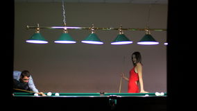A beautiful girl and young man playing billiards stock video