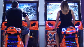 Beautiful girl and young man playing on slot machines - Motorcycle Racing stock video footage