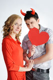 Beautiful girl with young man with red horns stock photography