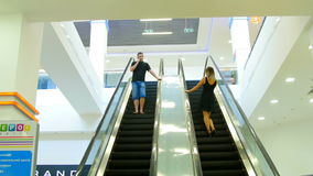 Beautiful girl and the young man saw each other on the escalator.  stock video footage