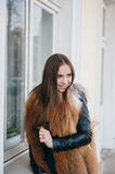 Beautiful girl. Young model walk around town in fur coats stock images