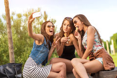 3 beautiful girlfriend eating ice cream while Selfie photo Stock Photos