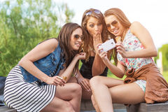 3 beautiful girlfriend watch the funny photos taken at.  Stock Photography
