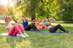 Exercising In Nature. Beautiful girlfriends doing sit-up in the park with female fitness trainer. Selective focus Royalty Free Stock Image