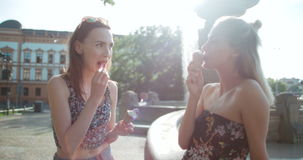 Beautiful girlfriends having fun in a city during sunny day. Two female friends eating ice cream and chatting in a city stock video