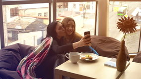 Beautiful girlfriends talking and taking pictures on the phone. Beautiful girlfriends sitting in chairs talking and taking pictures on the phone stock video footage