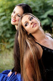 Beautiful girls. Two pretty girls sitting back to back Royalty Free Stock Photos