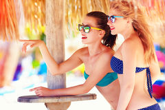 Beautiful girls in bikini talking on tropical beach, summer vacation Royalty Free Stock Photo