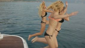Beautiful girls in bikinis having fun and jumping from the yacht into the sea. In slow motion stock video