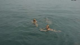 Beautiful girls in bikinis swimming and diving into the sea stock footage