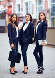 Beautiful girls in black suits posing on street Royalty Free Stock Images