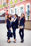 Beautiful girls in black suits posing on the street royalty free stock images