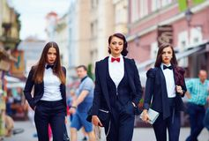 Beautiful girls in black suits walking the street Royalty Free Stock Images