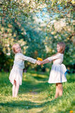 Beautiful girls in blooming apple tree garden enjoy warm spring day Stock Images