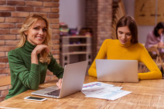 Beautiful girls in cafe. Two beautiful young girls in casual clothes smiling and using laptops, while working in cafe Royalty Free Stock Image