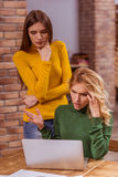 Beautiful girls in cafe. Two beautiful young girls in casual clothes using laptop, while working in cafe. Blonde girl is upset and confused Stock Images