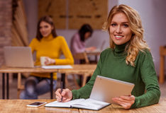 Beautiful girls in cafe. Beautiful young blonde girl in casual clothes using tablet and making notes, while working in cafe, in the background dark-haired girls Stock Photography