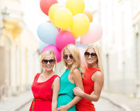 Beautiful girls with colorful balloons in the city Stock Images