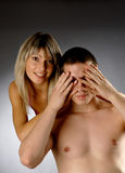 Beautiful girls covers eyes of half naked man Royalty Free Stock Photography