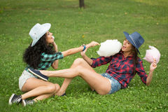 Beautiful girls in cowboy hats eating cotton candy Royalty Free Stock Photo