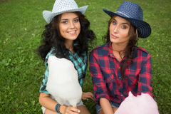 Beautiful girls in cowboy hats eating cotton candy Royalty Free Stock Image