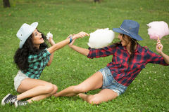 Beautiful girls in cowboy hats eating cotton candy Stock Photo