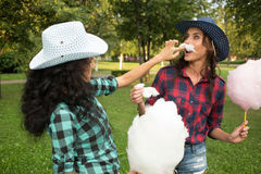 Beautiful girls in cowboy hats eating cotton candy Stock Image