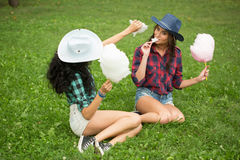 Beautiful girls in cowboy hats eating cotton candy Royalty Free Stock Photos