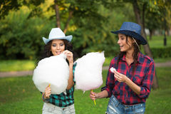 Beautiful girls in cowboy hats eating cotton candy Royalty Free Stock Images