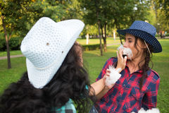 Beautiful girls in cowboy hats eating cotton candy Stock Photography
