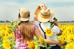 Beautiful Girls in a Cowboy Hats at the Sunflowers Field. Stock Photos
