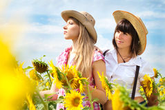 Beautiful Girls in a Cowboy Hats at the Sunflowers Field. Stock Images